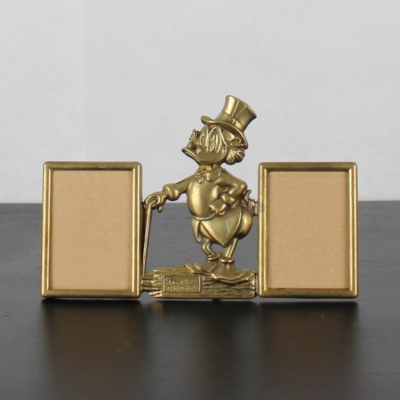 Vintage, brass double picture frame of Scrooge McDuck