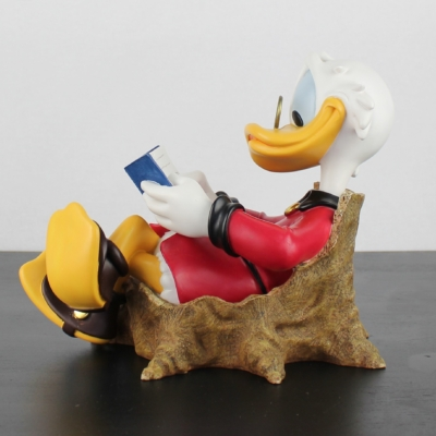Scrooge McDuck Sitting in a trea trunk and reading a book