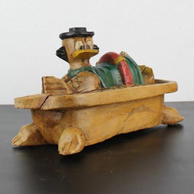 Vintage wooden statue of Scrooge McDuck bathing in money